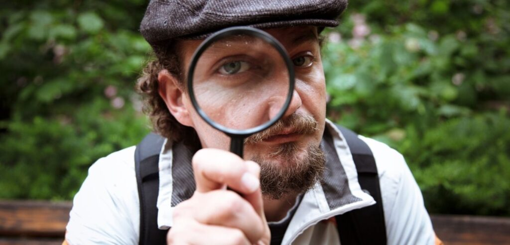 man with flat cap and magnify glass
